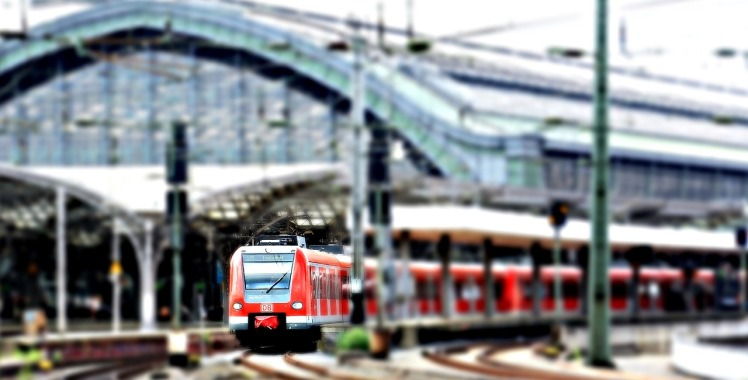 red train on tracks outside station, background blurred